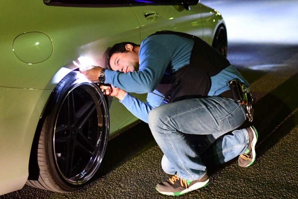 Ein Polizeibeamter nimmt ein getuntes Auto genauer unter die Lupe.