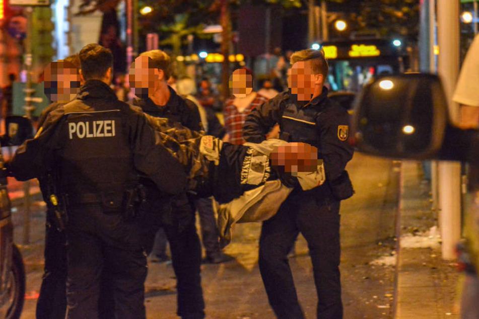 """An Händen und Füßen gefesselt brachten die Polizisten einen Mann aus der Gruppe aufs Revier. Augenzeugen beschrieben die Maßnahmen als """"unverhältnismäßig"""" und """"brutal""""."""