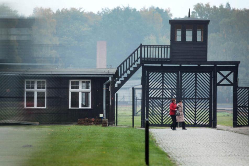 Zwei Besucher passieren den Eingang der KZ-Gedenkstätte. (Symbolbild)