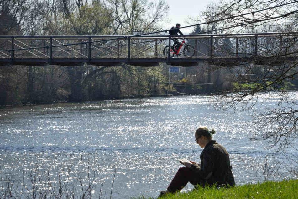 In Kassel genießt eine Frau an der Fulda die Sonne.