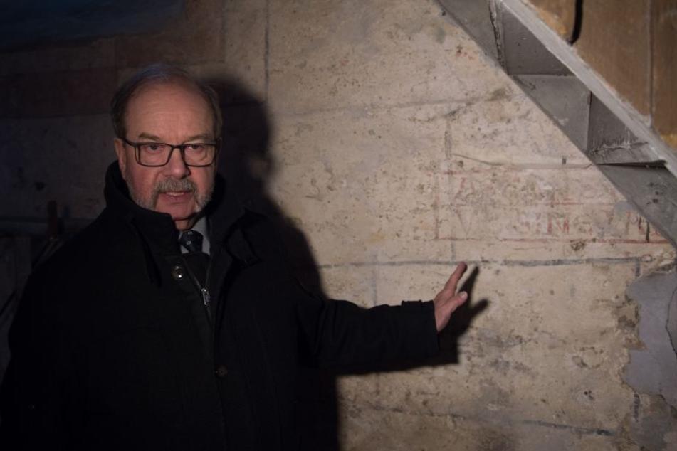 Kirchenvorstand Hans Beck zeigt die Schriften, die bisher durch Putz verdeckt waren.