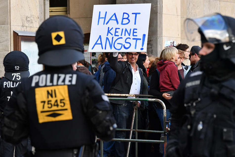 """Ein Gegendemonstrant hält am Rande einer Wahlkampfveranstaltung der AfD ein Schild mit der Aufschrift """"Habt keine Angst!"""" in der Hand."""