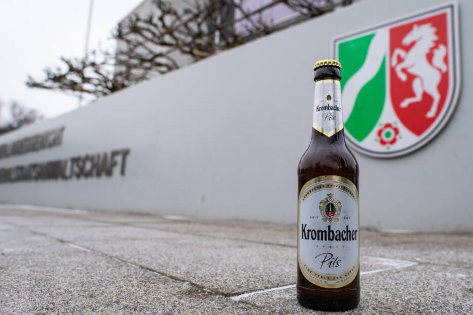 Eine Bierflasche von Krombacher vor dem Gericht.