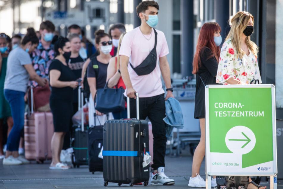 August 2020: Reiserückkehrer, vorwiegend aus Spanien, stehen mit Mundschutz vor dem Corona-Testzentrum am Flughafen Stuttgart.
