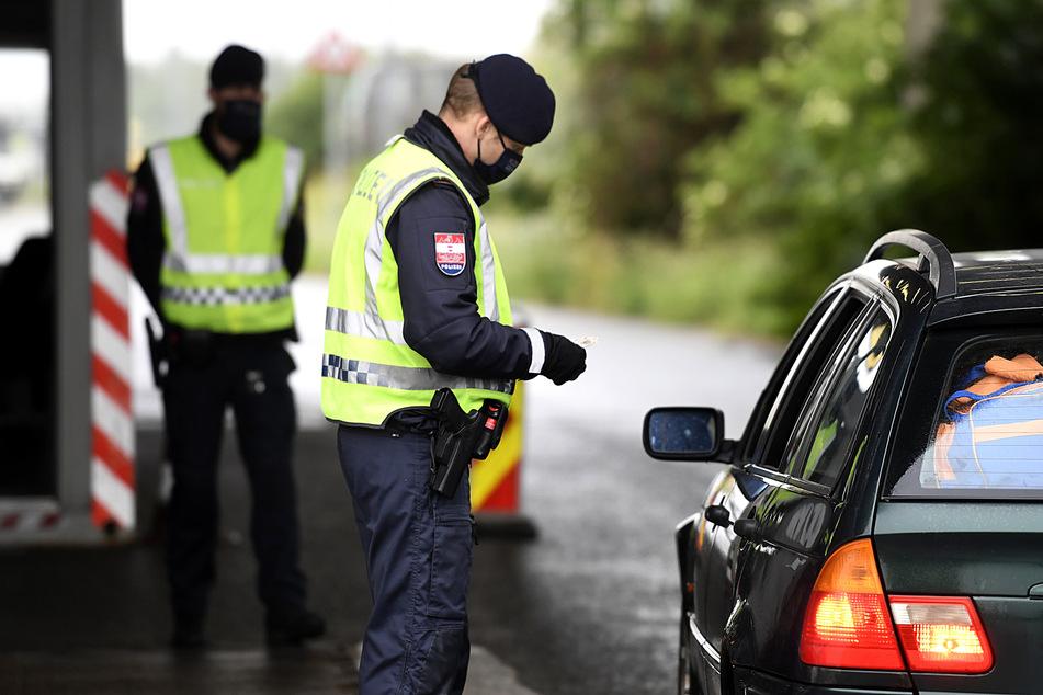 Ein Grenzbeamter kontrolliert an der österreichisch-ungarischen Grenze einen Autofahrer.