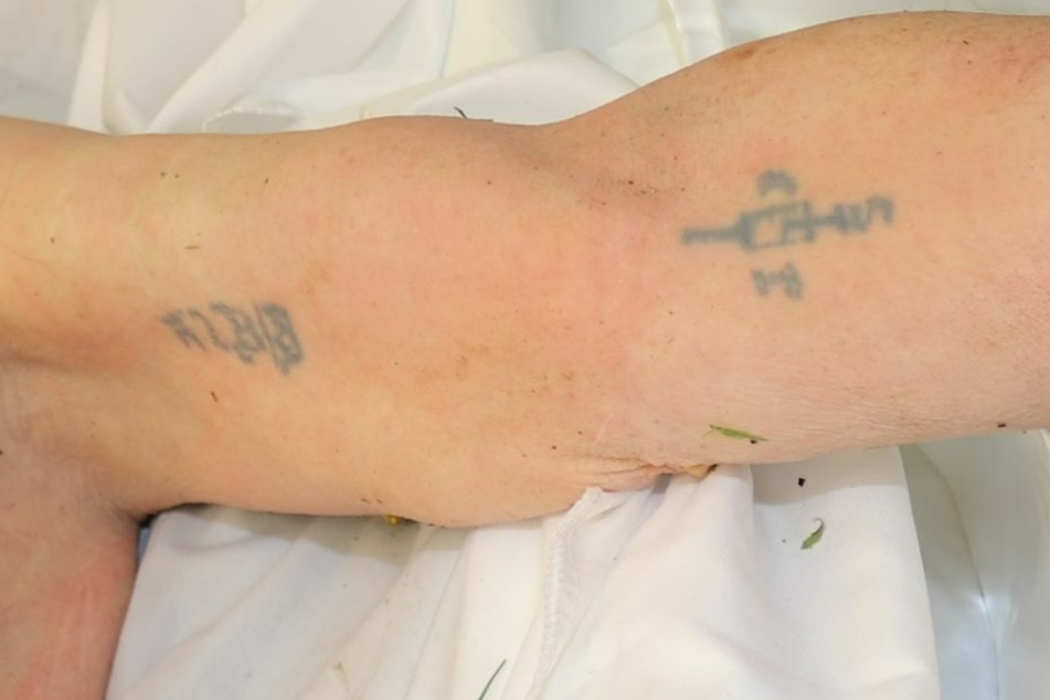 Auffällig sind zwei Tätowierungen auf der Innenseite des linken Ober- und Unterarmes des Unbekannten.