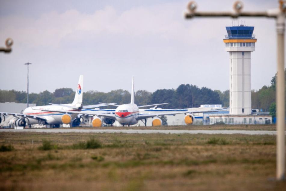 Zwei Airbus-Flugzeuge einer chinesischen Fluggesellschaft stehen auf einer Parkposition vor dem Tower des Airports. Seit Monaten tut sich dort kaum etwas.
