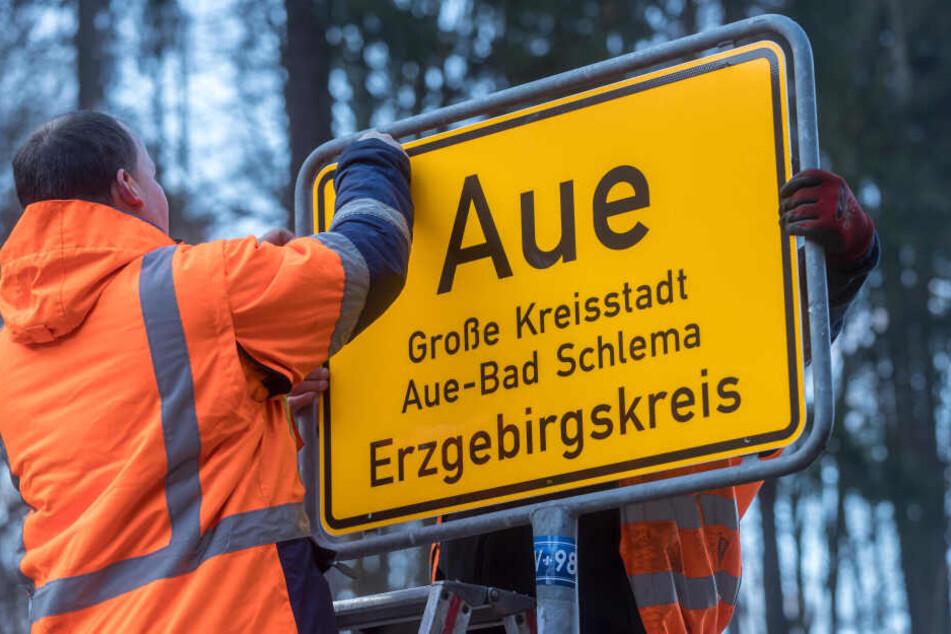 Neu gegen Alt: Hier wird eins von insgesamt 36 neuen Ortsschildern in Aue-Bad Schlema montiert.