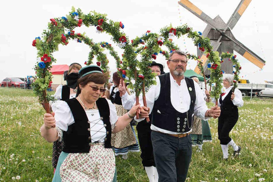 Traditionelle Trachten mit Blumentanzbögen vor einer Bockwindmühle: So ein Mühlenfest kann schonmal so richtig abgehen! (Symboldbild)