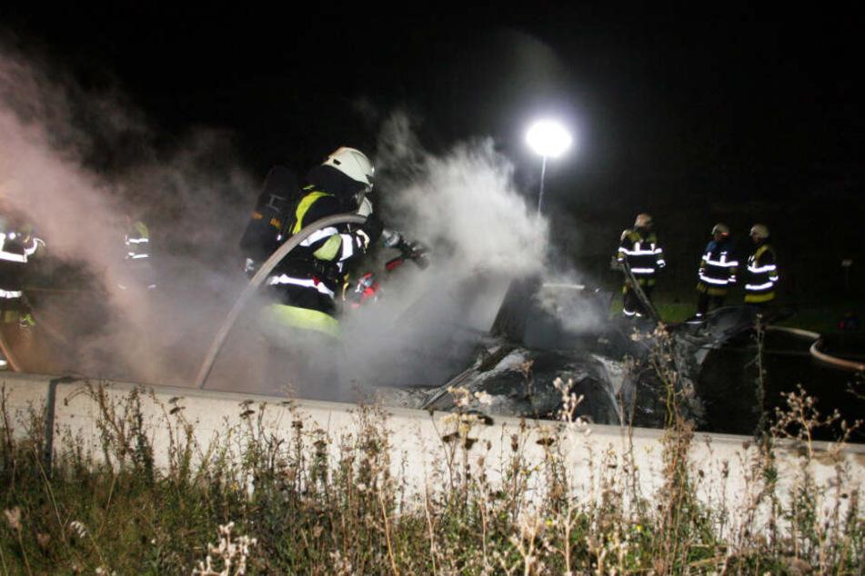 Die Feuerwehr löscht das brennende Auto.