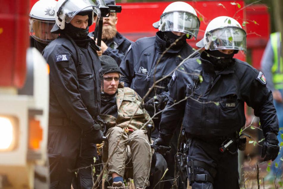 Polizisten nehmen eine Aktivistin in Gewahrsam.