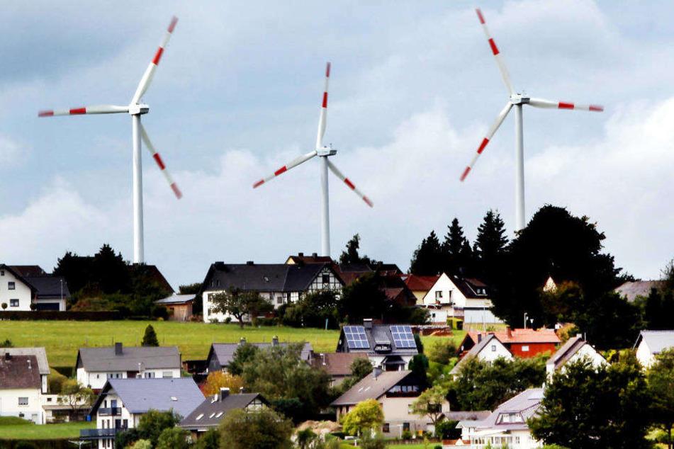 Windräder des Windparks Schöneseiffen in Gemünd drehen sich hinter Wohnhäusern.