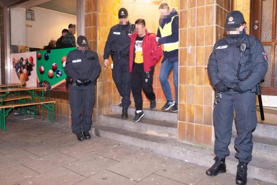 Polizisten führen einen festgenommenen Mann aus einem Kulturverein in Hamburg ab.