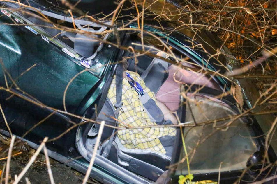 Ein Fahrzeug steckt in einer Böschung fest. Eine Person wurde eingeklemmt und befreit.