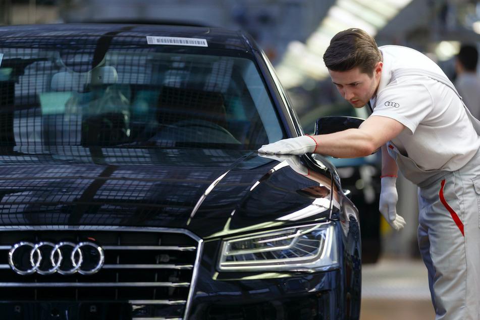 Ein Werksmitarbeiter kontrolliert in einer Produktionshalle von Audi an einem Bandende einen A8.