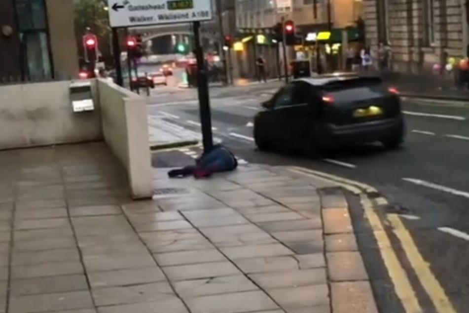 Der Mann knallt gegen ein Straßenschild und bleibt einen Moment liegen. Dann erhebt er sich. Scheinbar nicht schwer verletzt.
