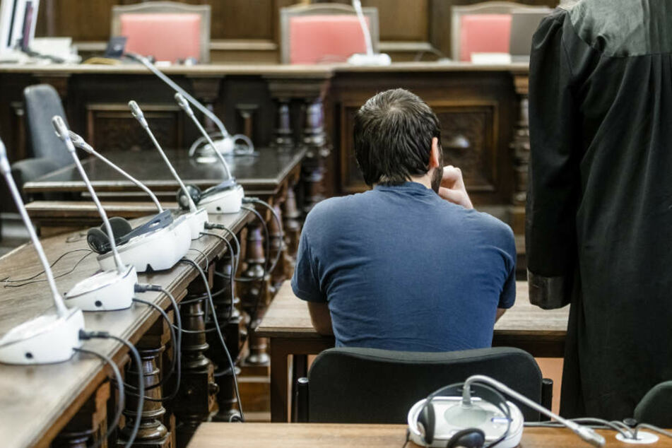 Der Angeklagte sitzt in einem Sitzungssaal des Strafjustizgebäudes.