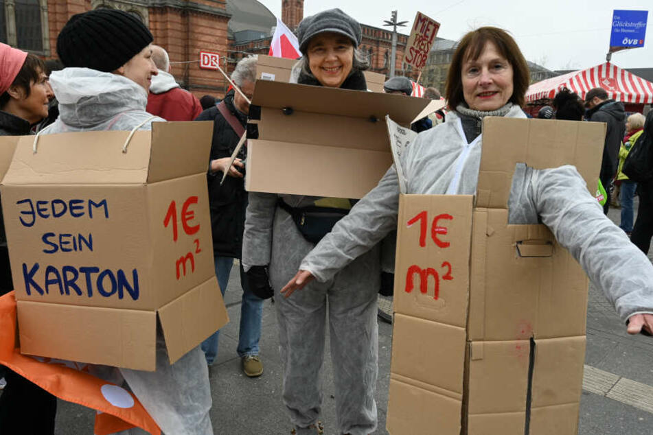 """Teilnehmer der Demonstration """"Die Stadt muss allen gehören"""", haben sich für mehr bezahlbaren Wohnraum Kartons angezogen."""
