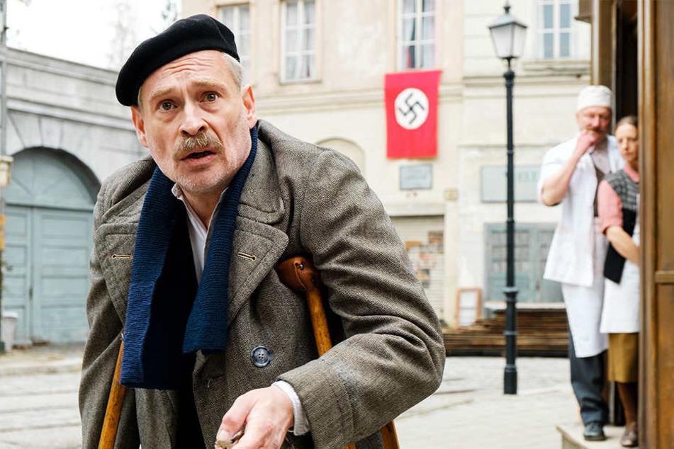Trafikant Otto Trsnjek (Johnannes Krisch) schaut fassungslos zu seinem Laden, der mit abstoßenden Schmierereien verwüstet wurde. Herr und Frau Metzger lachen sich vor der Hakenkreuzfahne ins Fäustchen.