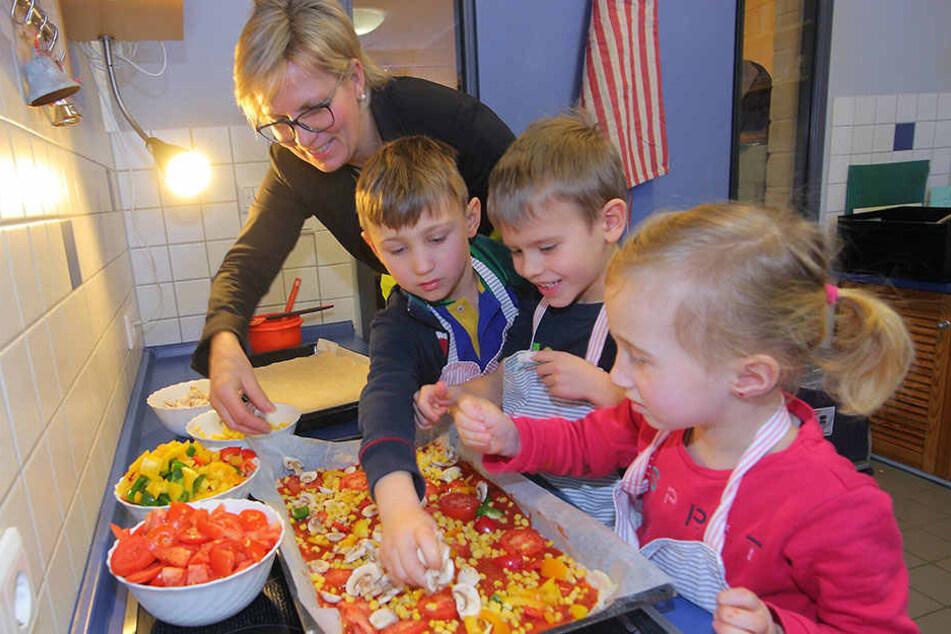 Sozialministerin Barbara Klepsch (52, CDU) hilft Moritz (6, v.l.) Leon (6) und Paula (4) beim Zubereiten der Pizza.