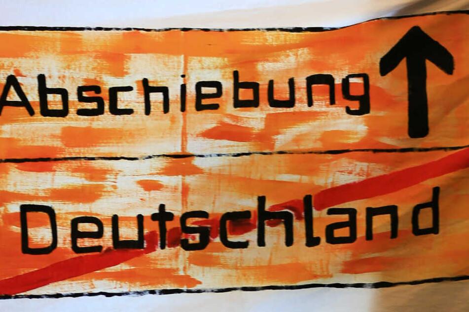 """Ein Protest-Transparent """"Abschiebung - Deutschland"""" hängt bei einer Pressekonferenz in einem Fenster. (Archivbild/Symbolbild)"""