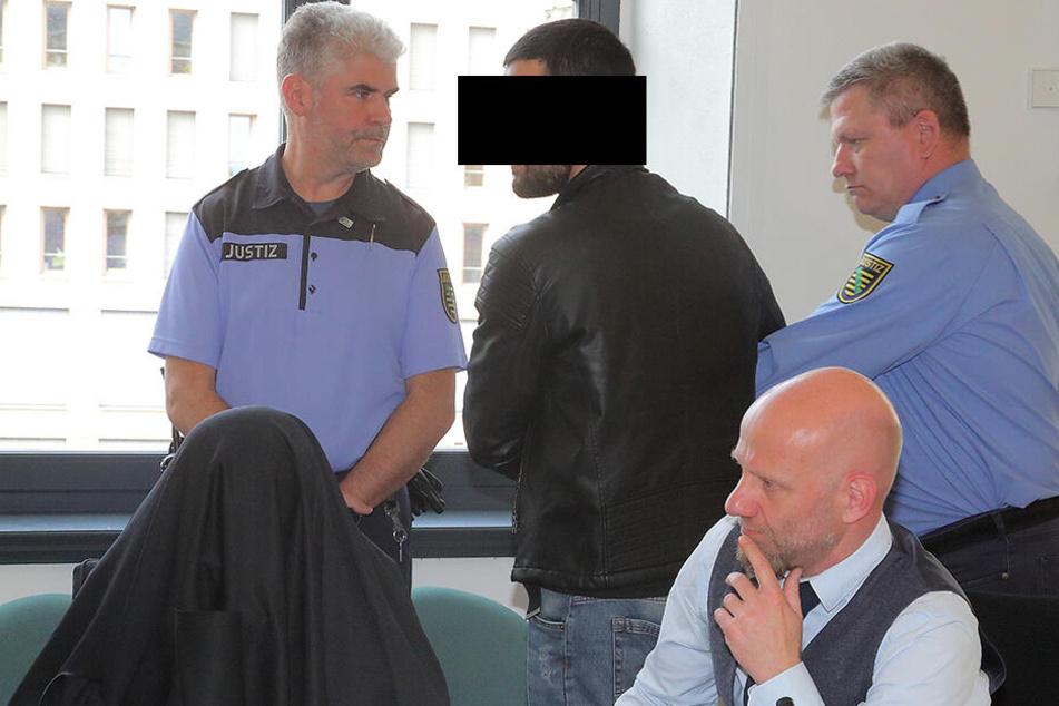Lasha S. (25, l.) versteckte sich beim Prozess unter einer schwarzen Jacke. Zurabi C. (26) wurde, wie alle drei Angeklagten, von Justizbediensteten vorgeführt.
