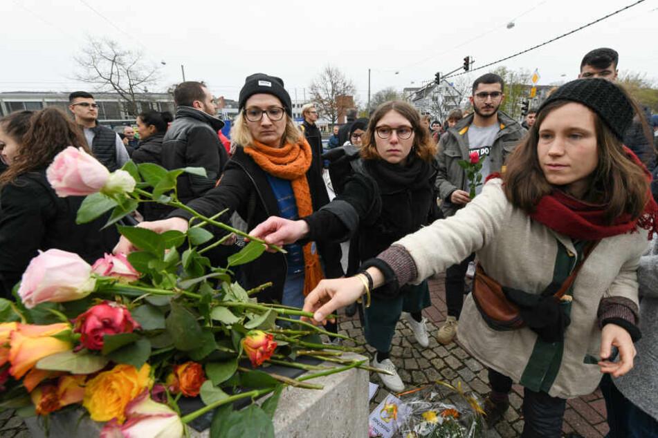 Menschen legen Blumen auf dem Halitplatz ab.