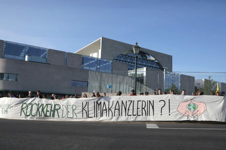 """Demonstranten halten ein Banner """"Rückkehr der Klimakanzlerin?!"""" beim Treffen des Koalitionsausschuss im Kanzleramt."""