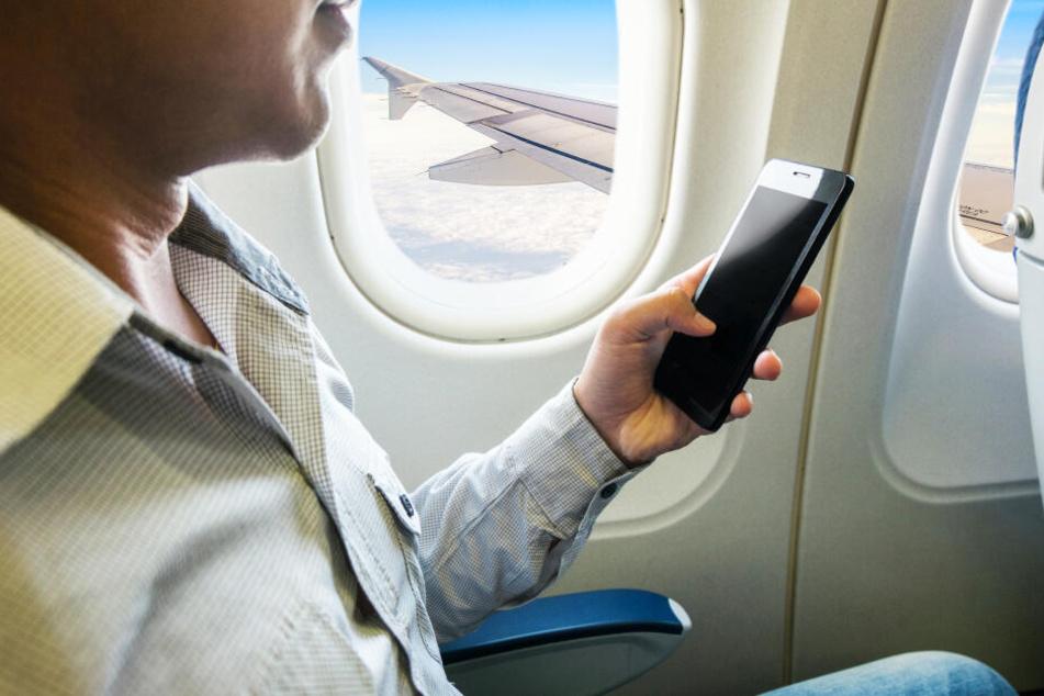 Ein Mann nutzt sein Handy im Flugzeug (Symbolbild).