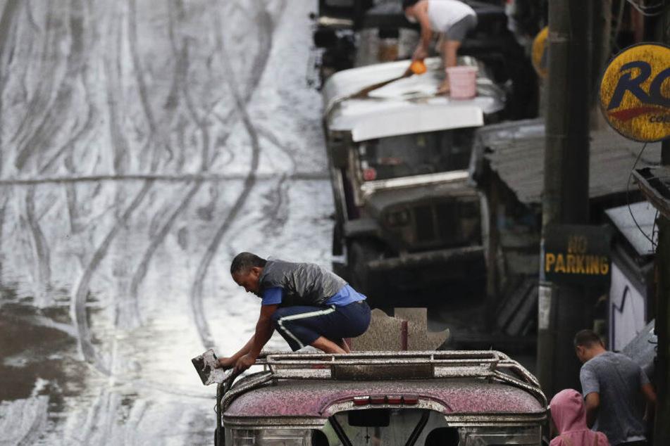 Anwohner reinigen ihre Fahrzeuge von Asche. Der südlich der philippinischen Hauptstadt Manila gelegene Vulkan Taal spuckt seit Sonntag Rauch und Asche.