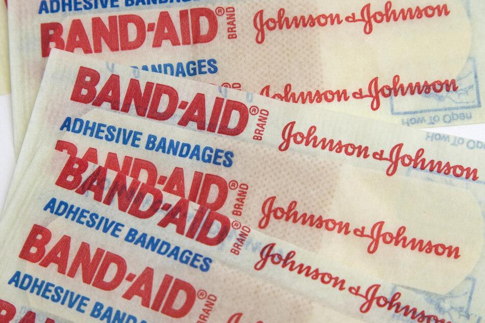 Pflaster des US-Pharmakonzern Johnson & Johnson liegen übereinander. Johnson & Johnson hat seine Studie für einen künftigen Corona-Impfstoff wegen einer ungeklärten Erkrankung eines Probanden vorübergehend unterbrochen.