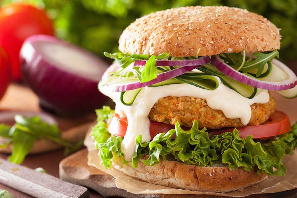 Vegetarischer Karotte-Hafer-Burger mit Gurke, Zwiebel und Tomate.