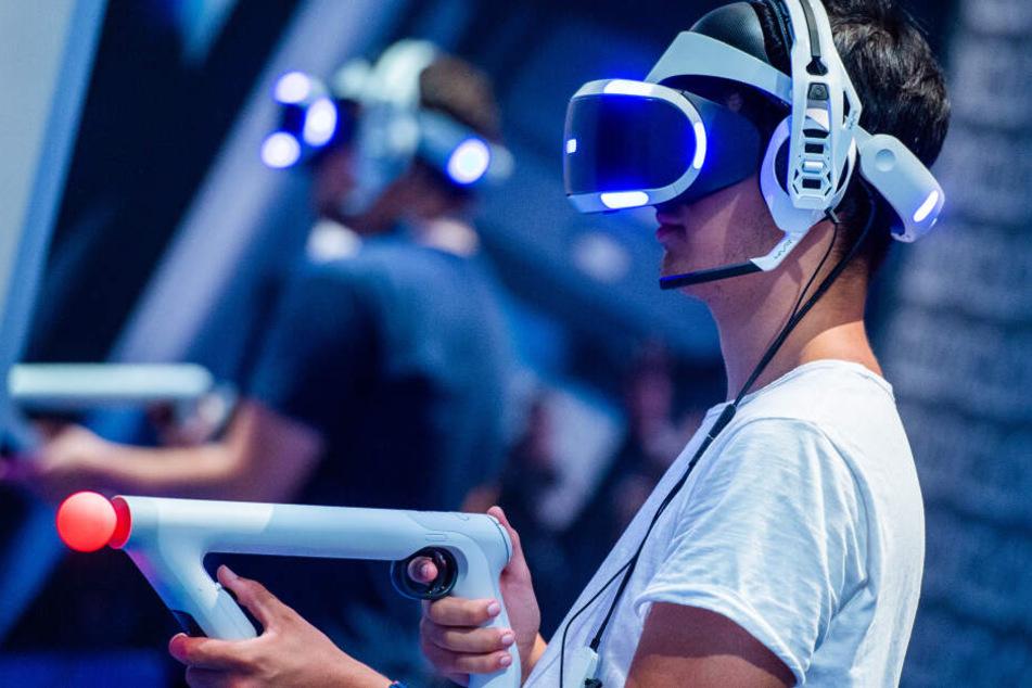 Ein Besucher der Gamescom 2018 probiert an einem Stand ein Videospiel mit einer VR-Brille aus.