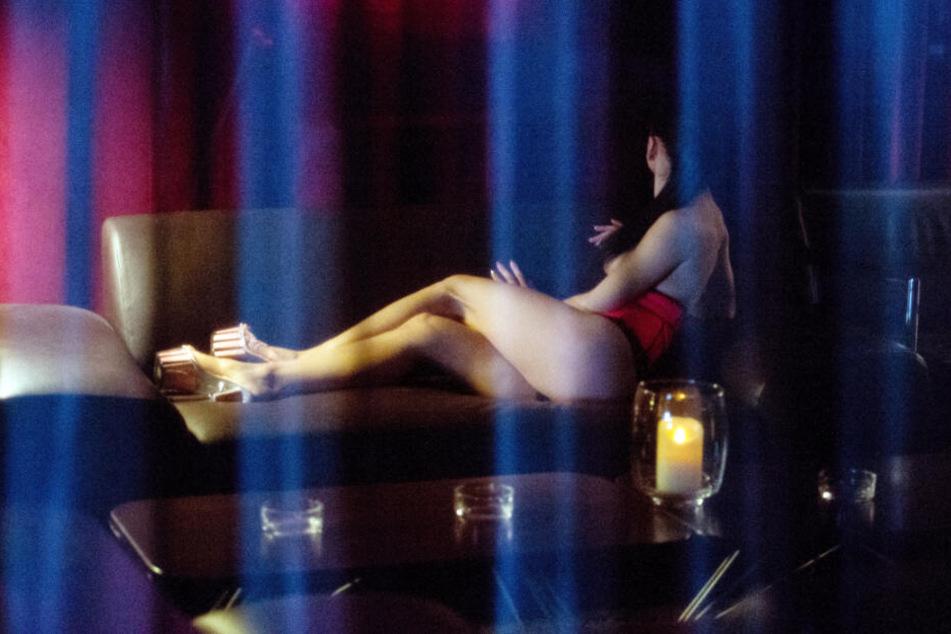 Eine spärlich bekleidete Prostituierte räkelt sich auf einem Sofa. (Archivbild)