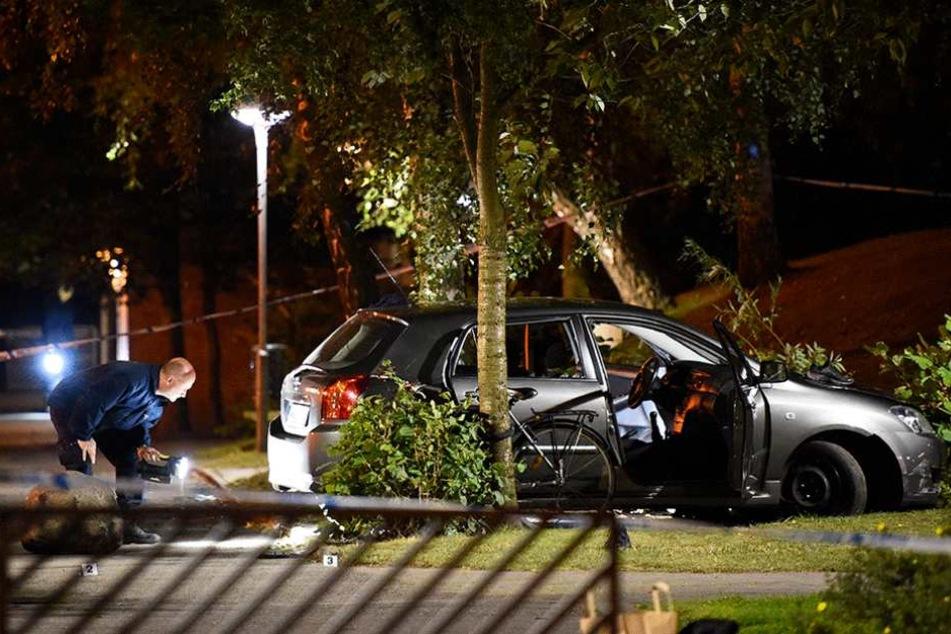 Polizisten untersuchen das beschossene Auto.