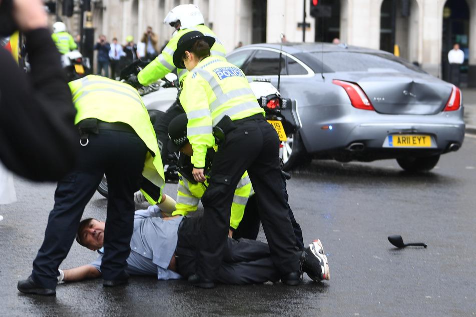 Polizeibeamte verhaften einen Mann, der zuvor vor das Auto des britischen Premierminister Johnson gelaufen ist.
