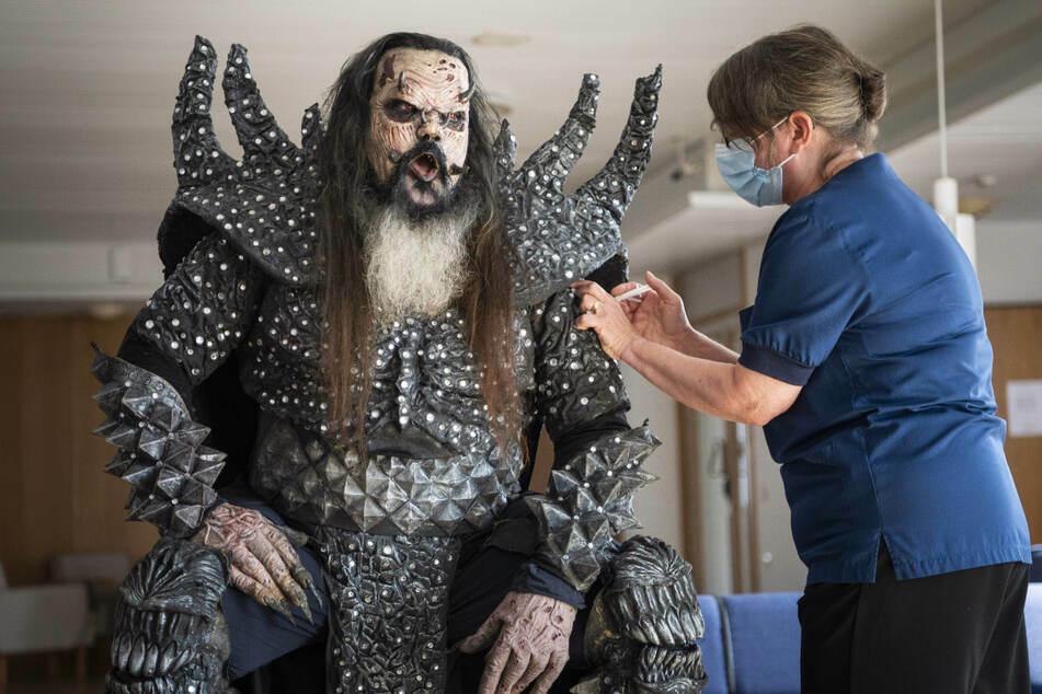 Mr. Lordi (47), Sänger der finnischen Hard-Rock-Band Lordi, wird von der Krankenschwester Paula Ylitalo die zweite Dosis eines Corona-Impfstoffs injiziert.