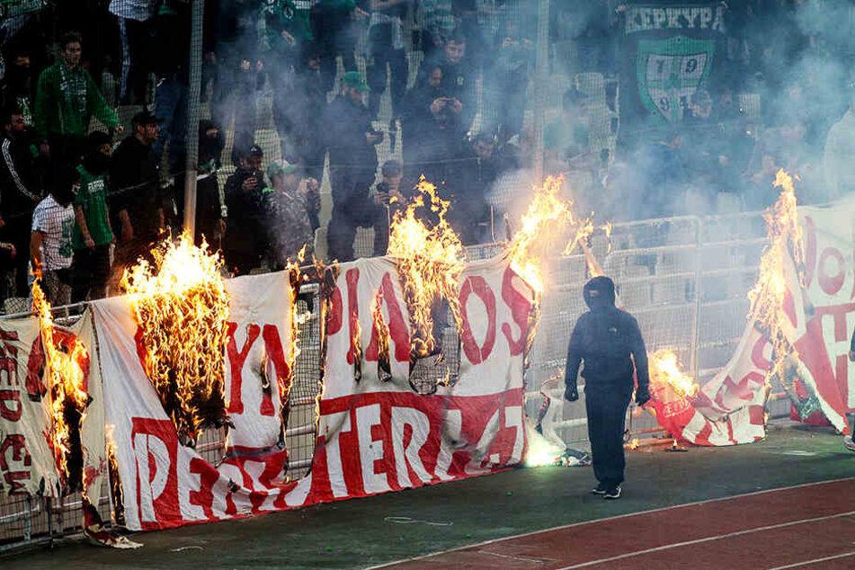 Vermummte Panathinaikos-Randalierer verbrennen ein Banner von Olympiakos Piräus.