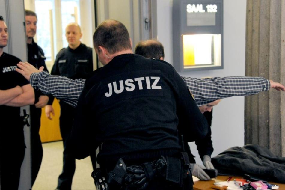 Justizbeamte kontrollieren Zuschauer im Kieler Landgericht.