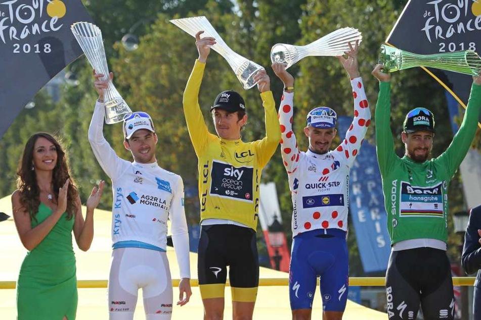Geraint Thomas (gelbes Trikot) mit seinem Pokal bei der Siegerehrung.