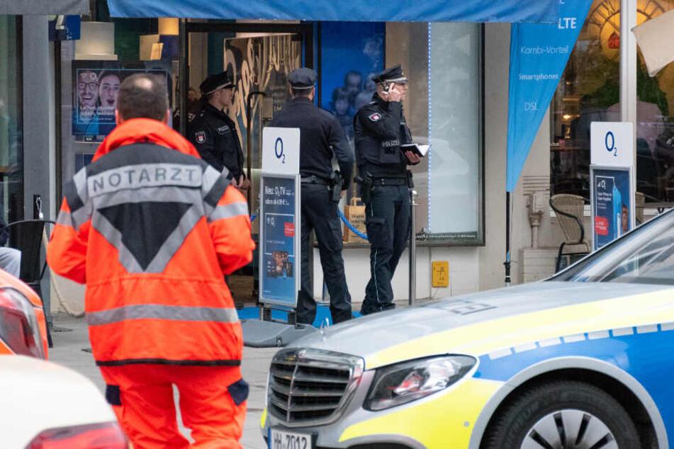 Die Polizei steht vor dem überfallenen Handy-Geschäft.