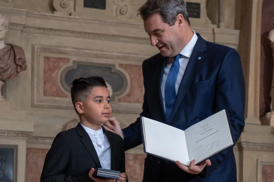 Kenan Büyükhan aus Nürnberg bekommt von Markus Söder (CSU), Ministerpräsident von Bayern, die Christophorus-Medaille überreicht.