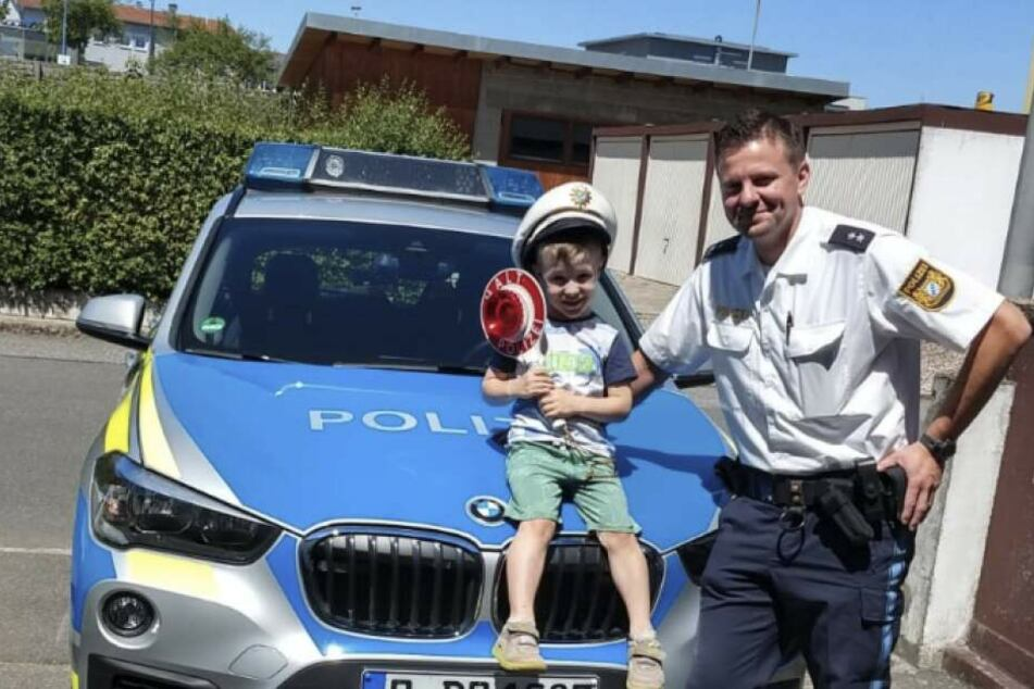 Die Polizisten haben ihr Versprechen eingelöst und sind mit dem Streifenwagen beim kleinen Jakob (l.) vorbeigefahren.
