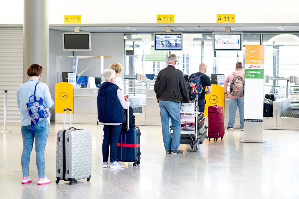Fluggäste stehen mit ihrem Gepäck vor einem Check-in-Schalter in der Abflughalle des Flughafens Hannover.