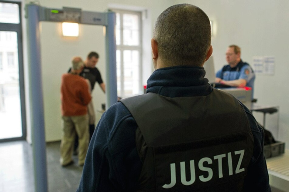 An einer Sicherheitskontrolle im Landgericht Potsdam überprüft ein Justizmitarbeiter einen Besucher.
