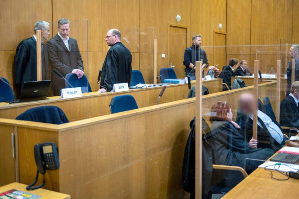 Der Angeklagte Stephan Ernst (hinten 2.v.l.) steht mit seinen Anwälten Mustafa Kaplan (hinten l.) und Jörg Hardies (hinten 3.v.l.) im Gerichtssaal im Oberlandesgericht Frankfurt.