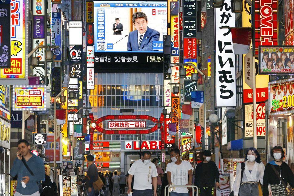 Eine große Leinwand in Tokio zeigt den japanischen Premierminister Shinzo Abe, das Ende des Ausnahmezustands verkündend, während Passanten mit Mundschutz auf der Straße entlanggehen.