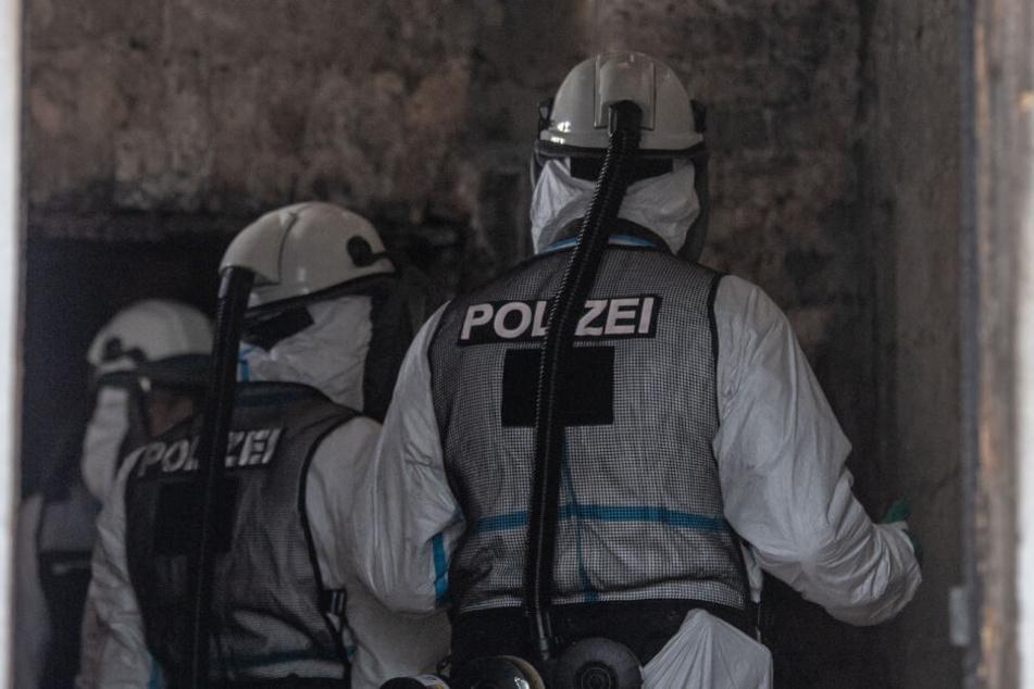 Kriminaltechniker in Atemschutzkleidung begutachten im ausgebrannten Haus ein Zimmer.