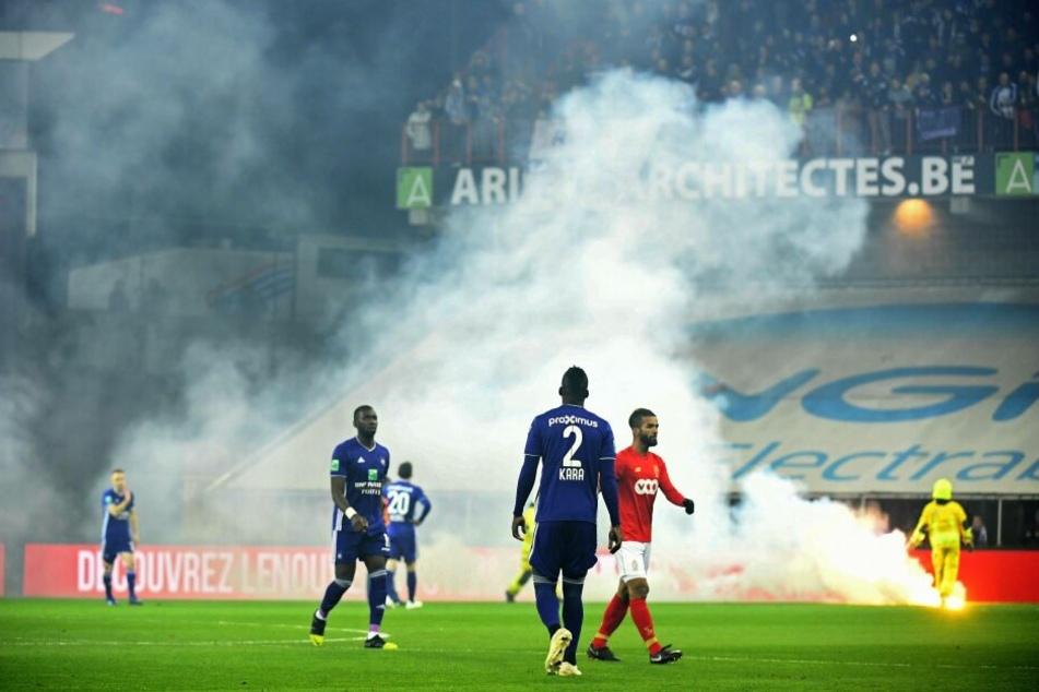 Die Spieler beider Mannschaften verlassen aufgrund der Raketen, die aufs Spielfeld fliegen, den Rasen.