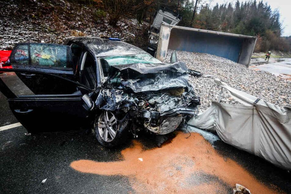 Bei einem schweren Verkehrsunfall auf einer glatten Straße ist die Beifahrerin eines Autos gestorben, nachdem ein Kieslaster umgekippt und mit dem Wagen kollidiert war.
